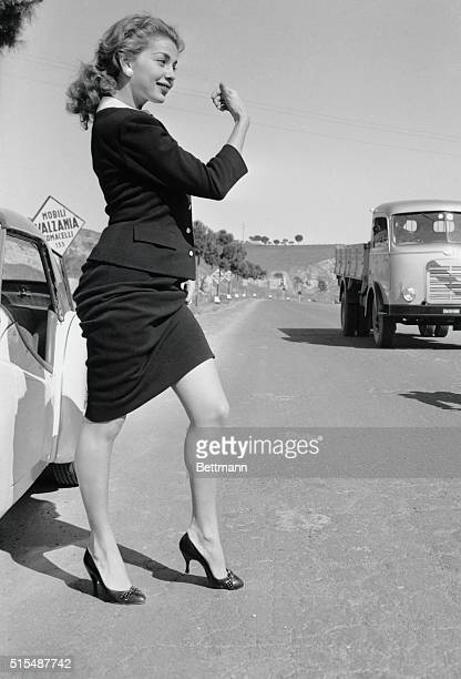 Singeractress Abbe Lane displays her shapely legs as she tries thumbing a ride after her car broke down during an outing in the outskirts of Rome...