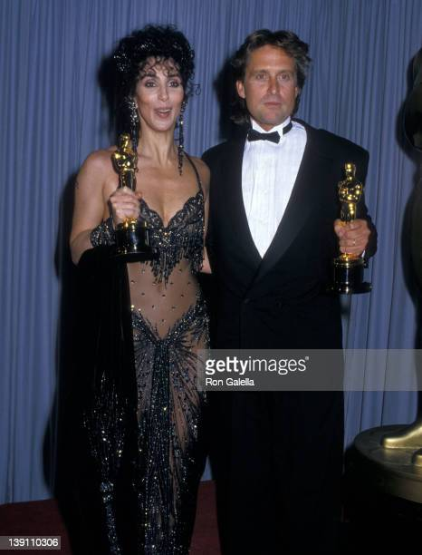 Singer/Actress Cher and actor Michael Douglas attend the 60th Annual Academy Awards on April 11 1988 at Shrine Auditorium in Los Angeles California