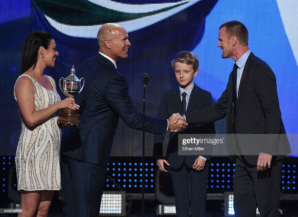 Singer/actress Tara Slone (L) and NHL Hall of Fame member Mark Messier (2nd L) present the King Clancy Memorial Trophy to Henrik Sedin (R) of the Vancouver Canucks as his his son Valter Sedin (2nd R) looks on during the 2016 NHL Awards at The Joint inside the Hard Rock Hotel & Casino on June 22, 2016 in Las Vegas, Nevada.