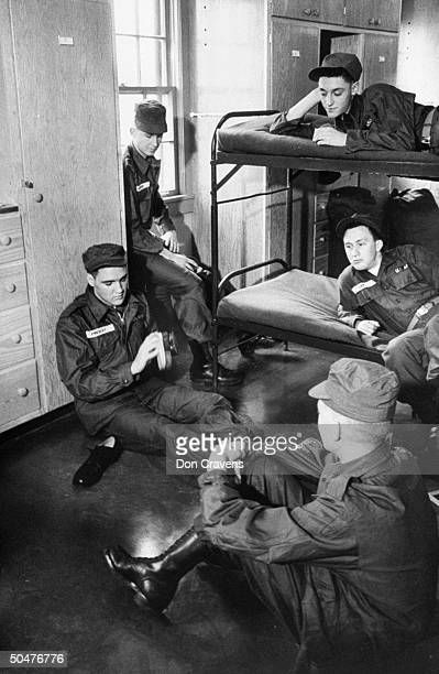 Singer/Army Pvt. Elvis Presley clad in Army fatigues & cap, sitting on barrack floor as he brush-polishes his Army shoes while 4 other inductees look...