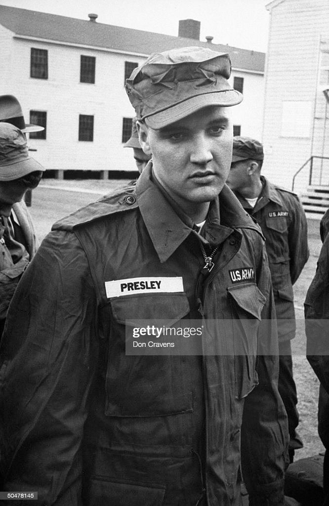 Singer/Army Pvt. Elvis Presley clad in Army fatigues & cap, standing around w. several inductees outside barracks at Ft. Chaffee reception center.