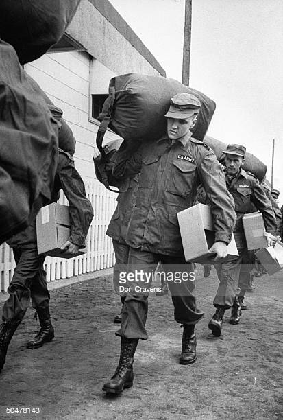 Singer/Army Pvt. Elvis Presley clad in Army fatigues & cap, w. Duffel bag over his shoulder & box under one arm, w. Several inductees as they walk to...
