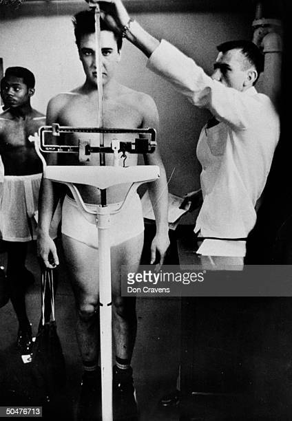 Singer/Army Pvt. Elvis Presley clad only in his skivvies as he stands on scale while Army doctor measures his height at 6 1/2 at pre-induction...