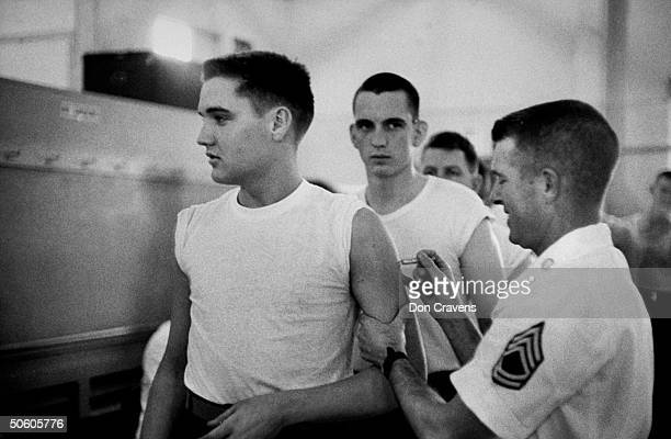 Singer/Army Pvt. Elvis Presley in t-shirt, w. Others getting shot fr. Army doctor during his pre-induction physical at Kennedy Veterans Hospital.
