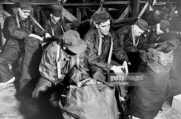 Singer/Army Pvt. Elvis Presley wearing Army fatigues as he tries on shoes while sitting nr. His duffel bag on bench w. Six other new inductees into...