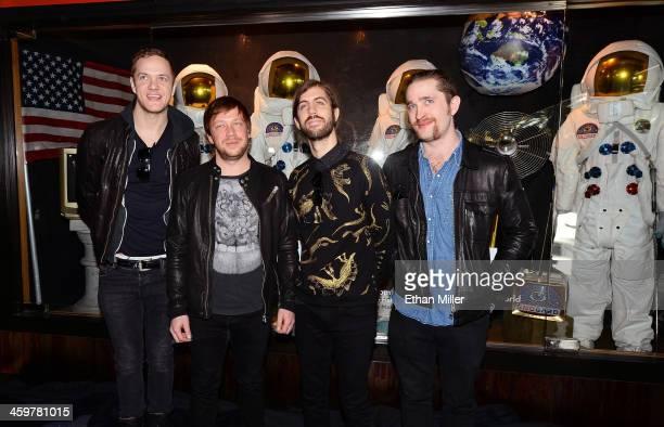 Singer/drummer Dan Reynolds bassist Ben McKee guitarist Wayne Sermon and drummer Daniel Platzman of Imagine Dragons appear at a memorabilia case...
