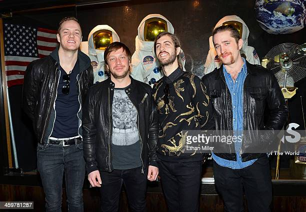 Singer/drummer Dan Reynolds bassist Ben McKee guitarist Wayne Sermon and drummer Daniel Platzman of Imagine Dragons appear at a memorabilia case...