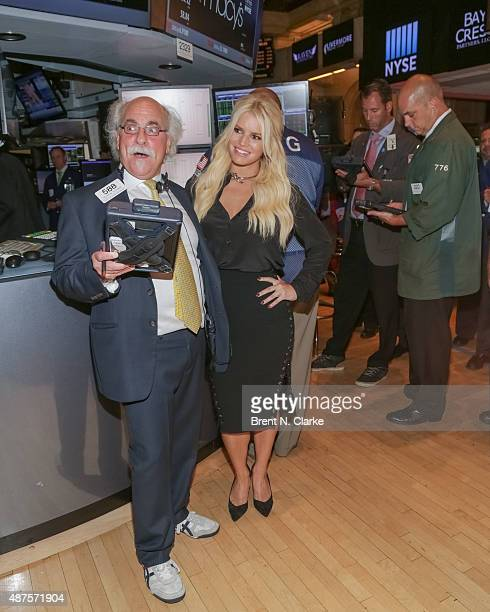 Singer/fashion designer Jessica Simpson poses for photographs with trader Peter Tuchman after ringing the New York Stock Exchange opening bell at the...