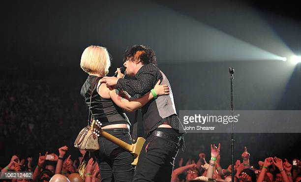 Singer/guitarist Billie Joe Armstrong of Green Day performs with audience member at The Forum on August 25 2009 in Inglewood California