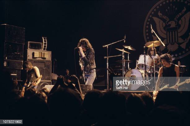 Singerguitarist Joan Jett watches from the wings as guitarist Johnny Ramone singer Joey Ramone drummer Tommy Ramone and bassist Dee Dee Ramone of the...