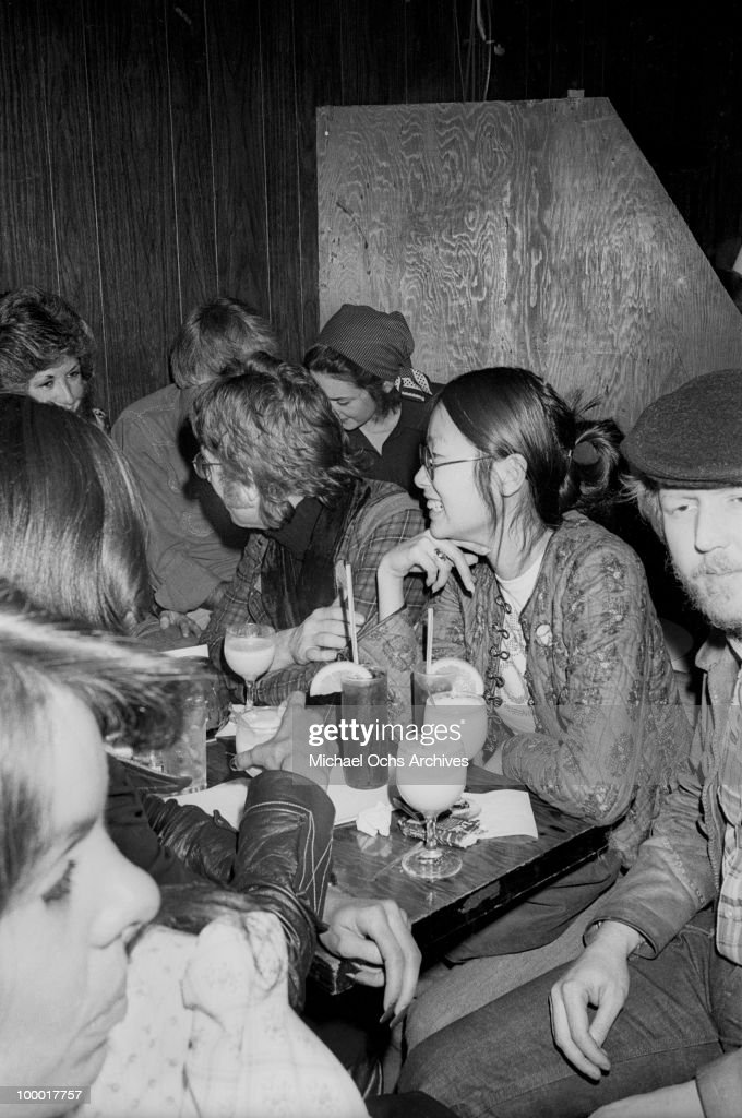 Singer-guitarist John Lennon, formerly of The Beatles, attends a Smothers Brothers comedy performance with girlfriend May Pang and fellow singer-songwriter Harry Nilsson (right), during Lennon's infamous 'Lost Weekend' period, at the Troubadour on March 12, 1974, in West Hollywood, California. Lennon and Nilsson would later be kicked out of the show for drunken heckling.