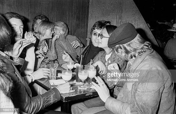 Singerguitarist John Lennon formerly of The Beatles attends a Smothers Brothers comedy performance with girlfriend May Pang Peter Lawford Jack Haley...