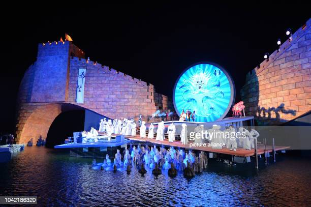 Singers and extras perform in front of a scenery depicting the Chinese Wall on the floating stage during a photo rehearsal of the opera 'Turandot' in...