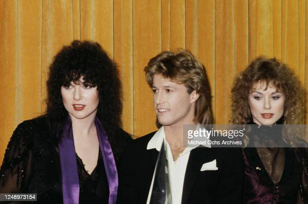 Singers Ann and Nancy Wilson of the rock band Heart with singer Andy Gibb at the American Music Awards, USA, 18th January 1980. Gibb is accepting the...