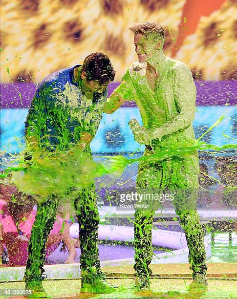 Singers Austin Mahone and Cody Simpson get slimed onstage during Nickelodeon's 27th Annual Kids' Choice Awards held at USC Galen Center on March 29...