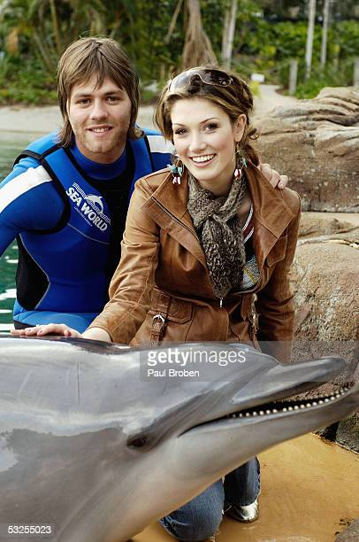 Singers Delta Goodrem and Brian McFadden play with dolphins at Sea World on July 19 2005 in Main Beach Gold Coast Australia