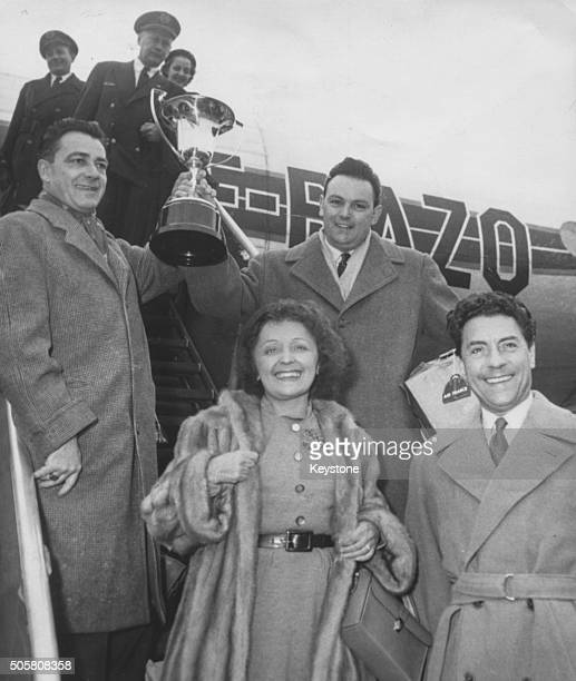 Singers Edith Piaf and Jacques Pills pictured stepping from an airplane followed by racing driver Rene Bonnet and politician Andre Moynet as they all...