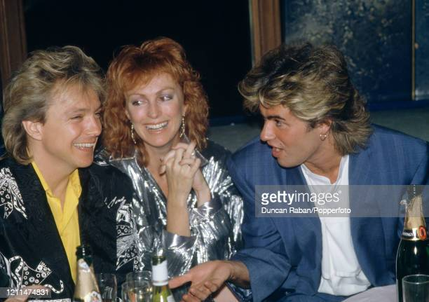 Singers George Michael and David Cassidy with Cassidy's wife Meryl Tanz after the premiere of the film Number One in London England circa April 1985