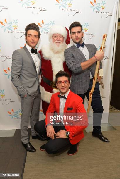 Singers Gianluca Ginoble Piero Barone and Ignazio Boschetto of Il Vilo pose with Santa Claus backstage at the unveiling of the HGTV Holiday House at...