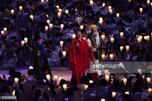 TOPSHOT Singers Ha Hyunwoo Lee Eunmi Jeon Inkwon and An Jiyeong perform onstage surrounded by people holding candles during the opening ceremony of...