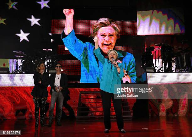 Singers Jennifer Lopez and Marc Anthony look on as Democratic presidential nominee former Secretary of State Hillary Clinton speaks during a Get Out...