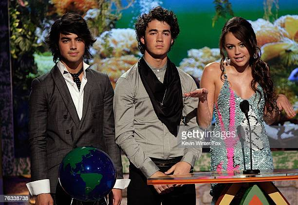 Singers Joe Jonas Nick Jonas and actress Miley Cyrus present the 'Choice RB Track' award onstage during the 2007 Teen Choice Awards held at The...