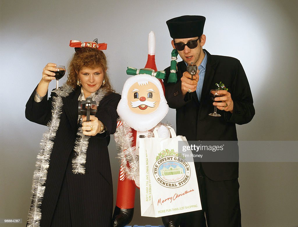 Singers Kirsty MacColl (1959 - 2000) and Shane MacGowan with with toy guns and an inflatable Santa in a festive scenario, circa 1987. In 1987, the pair collaborated on the Pogues' Christmas song 'Fairytale of New York'.