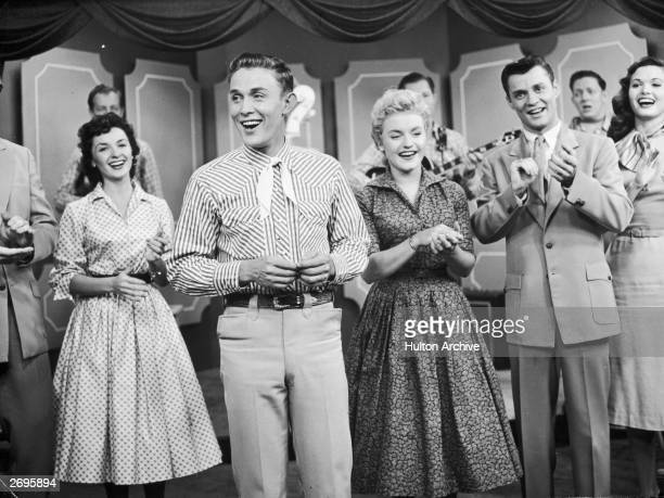 Singers Mary Klick Jimmy Dean J Davis and Jan Crockel perform in front of musicians on a stage possibly in a still from the television series 'The...