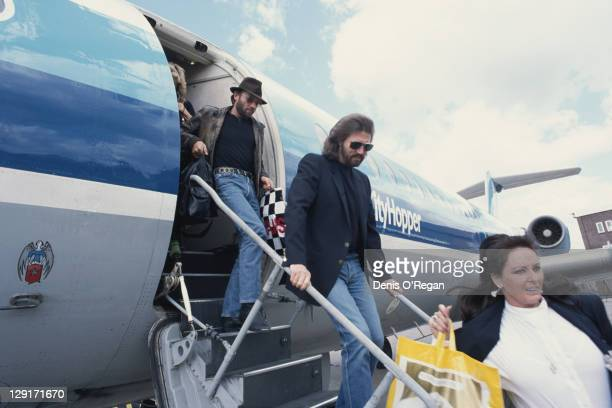 Singers Maurice and Barry Gibb of the Bee Gees disembarking from an airliner circa 1990
