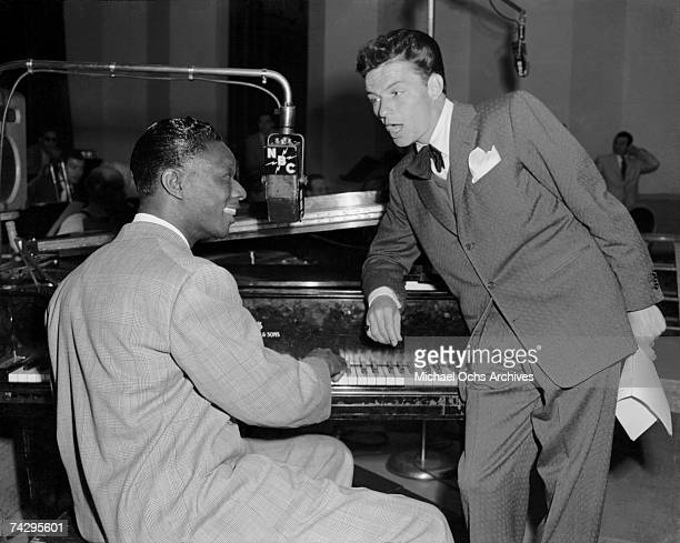 Singers Nat King Cole and Frank Sinatra sing in to a vintage NBC microphone at the piano on February 15 1946 in Los Angeles California