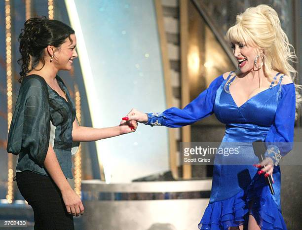 Singers Norah Jones and Dolly Parton share a moment onstage at the 37th Annual CMA Awards at the Grand Ole Opry House November 5 2003 in Nashville...