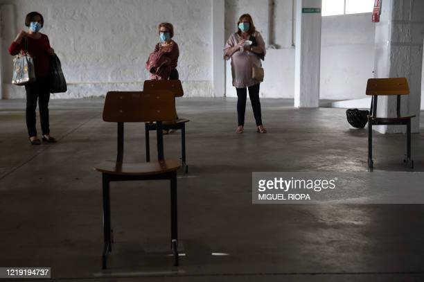 Singers of the Apostol Santiago choir wearing face masks arrive to attend the first rehearsal after the loosening of a national lockdown to stop the...