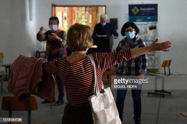 Singers of the Apostol Santiago choir wearing face masks greet each other as they arrive to attend the first rehearsal after the loosening of a...