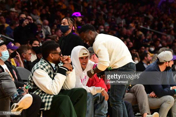 Singers Usher and Justin Bieber talk to Entertainer, Kevin Hart during a game between the Golden State Warriors and the Los Angeles Lakers on October...