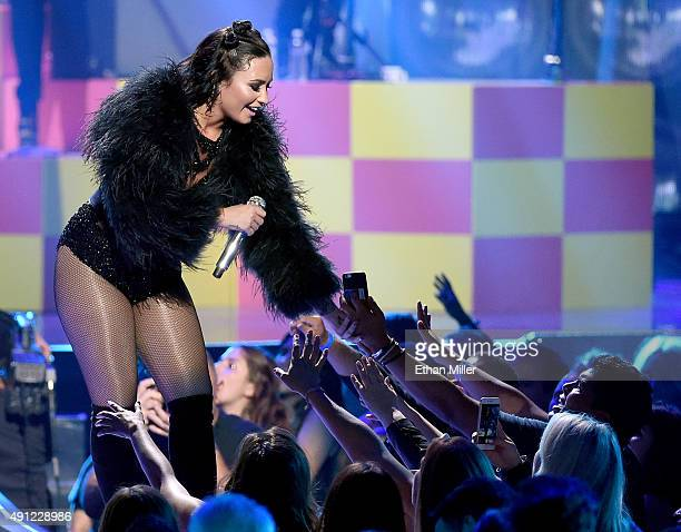 Singer/songwriter and actress Demi Lovato reaches out to fans as she performs at the 2015 iHeartRadio Music Festival at MGM Grand Garden Arena on...