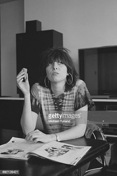Singersongwriter and guitarist Chrissie Hynde of American rock group The Pretenders relaxing with an ice cream and a magazine London September 1986