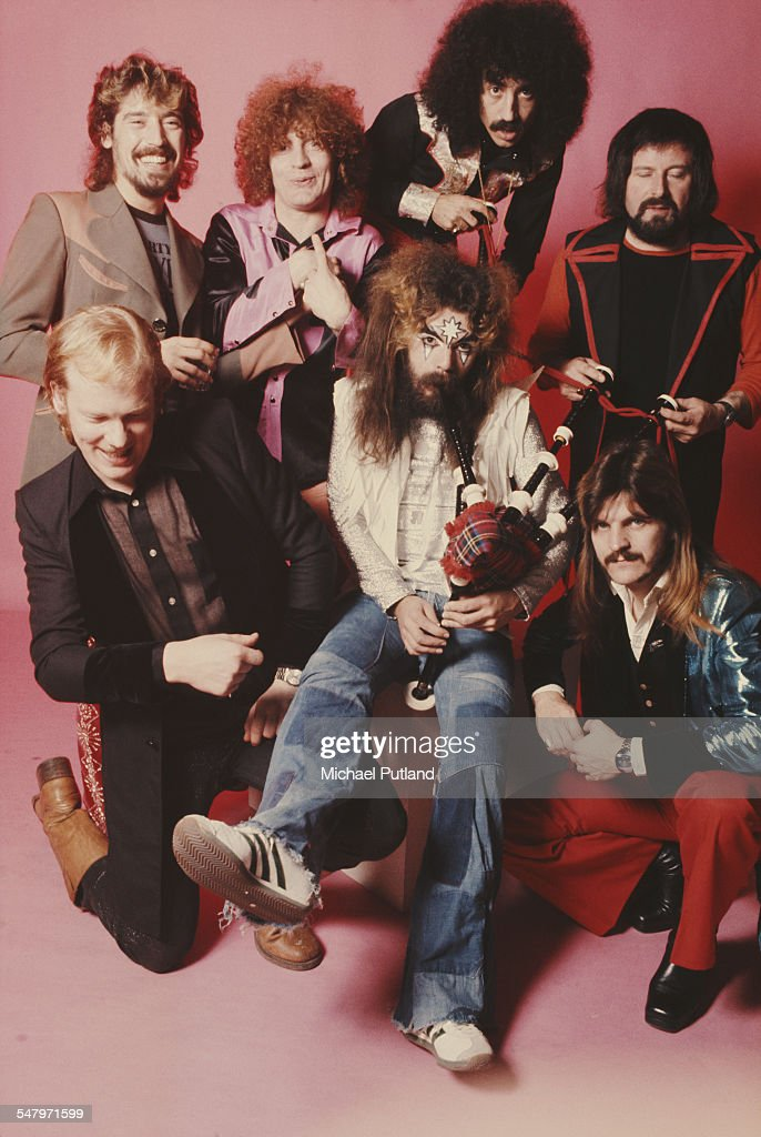 Singer-songwriter and musician Roy Wood plays the bagpipes (centre), surrounded by the other members of English pop group Wizzard, London, 6th December 1974. Clockwise, from front left: saxophonist Nick Pentelow, drummer Keith Smart, keyboard player Bob Brady, drummer Charlie Grima, saxophonist Mike Burney, bassist Rick Price and Roy Wood.