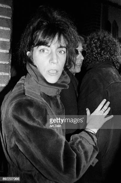 Singersongwriter and poet Patti Smith is caught by surprise as she enters a building with friends New York City 1980