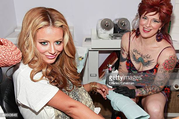 Singer/songwriter Aubrey O'Day is tattooed by tattoo artist Friday Jones during the opening of Friday Jones Fifth Ave Tattoo Studio at Senses NY...