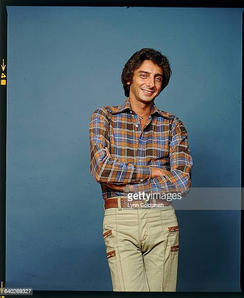 Singer/songwriter Barry Manilow is shown posed in a studio portrait he wears a flannel shirt and tan pants with a brown woven belt Undated