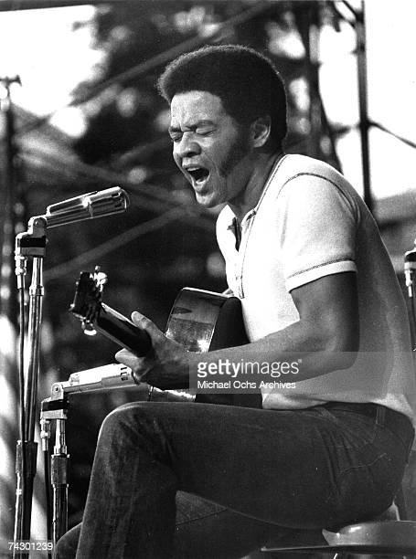 Singer/songwriter Bill Withers performs onstage with an acoustic guitar in circa 1973.