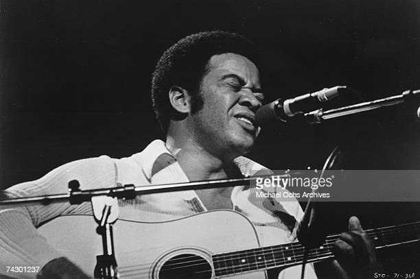 "Singer/songwriter Bill Withers plays acoustic guitar as he performs onstage at the ""Save The Children"" concert which was turned in to a movie of the..."