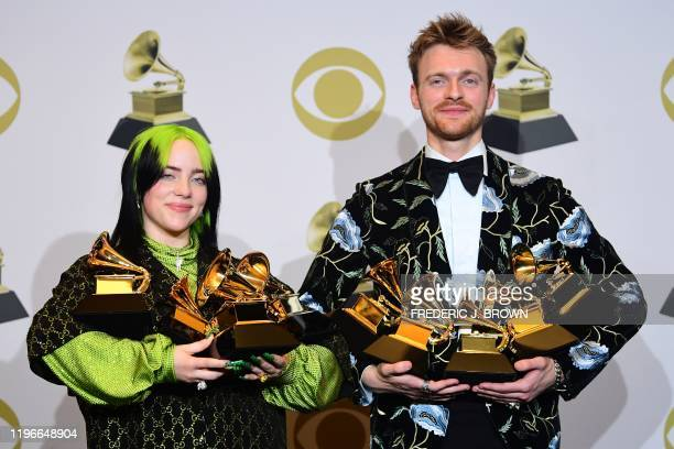 Singer-songwriter Billie Eilish and Finneas O'Connell pose in the press room with the awards for Album Of The Year, Record Of The Year, Best New...