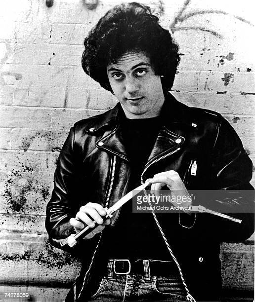 Singer/songwriter Billy Joel wears a leather motorocycle style jacket as he cleans his nails with a switchblade knife in circa 1977 Photo by Michael...