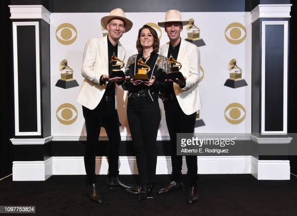 Singer/songwriter Brandi Carlile with musicians Tim and Phil Hanseroth poses with her awards for Best American Roots Performance 'The Joke' Best...