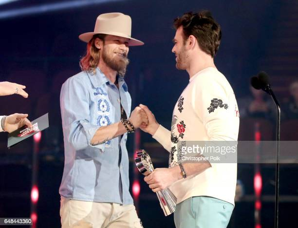 Singersongwriter Brian Kelley of music group Florida Georgia Line presents the Brand New Artist award to recording artist Alex Pall of music group...