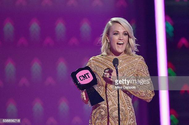 Singersongwriter Carrie Underwood accepts an award onstage during the 2016 CMT Music awards at the Bridgestone Arena on June 8 2016 in Nashville...