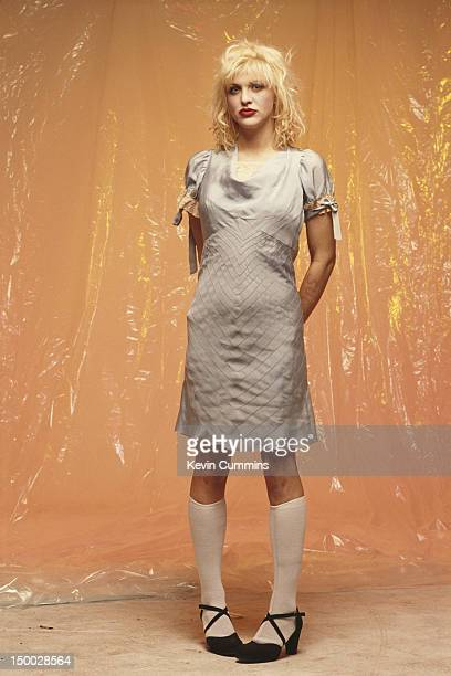 Singersongwriter Courtney Love of American alternative rock group Hole wearing a dress and kneelength socks March 1993