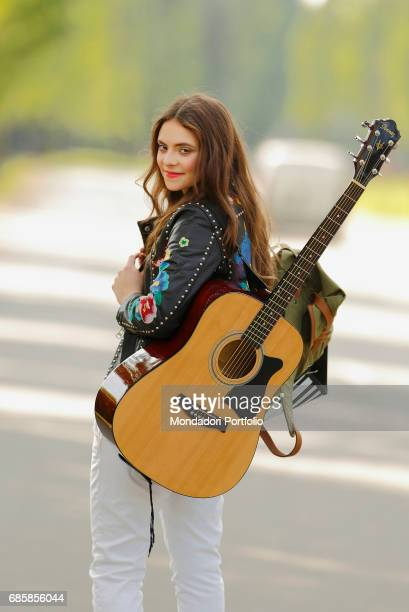 Singersongwriter Francesca Michielin with a guitar on her back on the avenue leading to Palazzo Mondadori Segrate Italy 20th April 2016