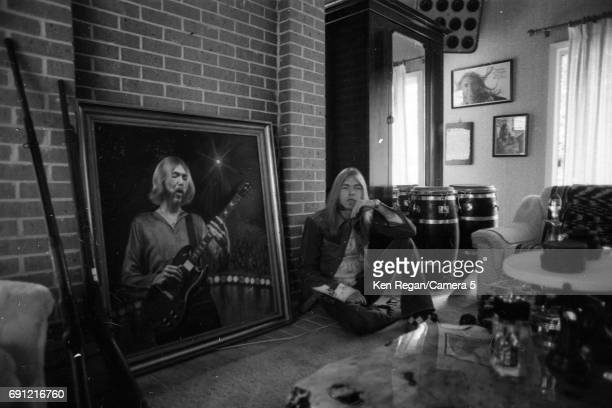 Singer/songwriter Gregg Allman of the Allman Brothers Band is photographed with portrait of his brother Duane Allman at home in August 1975 CREDIT...